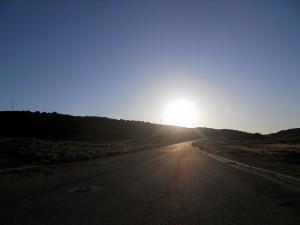 Route qui avance vers le soleil à l'horizon : vers une nouvelle vie ?